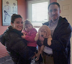 family with their new puppies